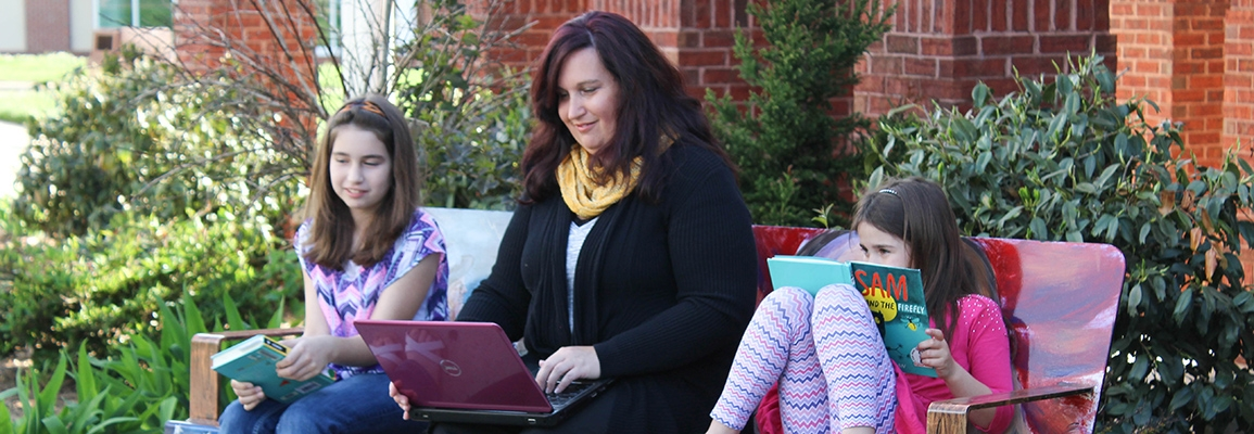 Woman using laptop computer while sitting outside with her daughters